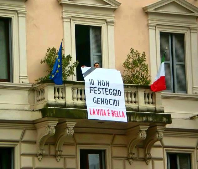 Gaetano Siciliano espone un cartellone a Roma (cortesia di eleaml.org)